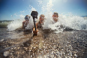 Brothers and sister are having fun in sea. Kids are lying on the front and being splashed by waves. Kids are holding a waterproof action camera on a selfie stick and filming themselves.\nNikon D850