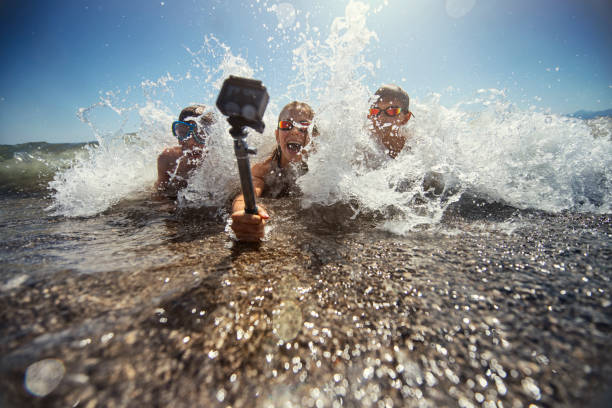 Kids playing in sea waves and filming themselves using waterproof action camera. stock photo