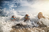 Brothers and sister are having fun on the beach. Kids are lying on the beach and they are splashed by big sea waves.\nNikon D850