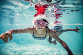 Little girl and her brother are having fun swimming underwater during summer Christmas.  Kids are wearing santa's hats.
