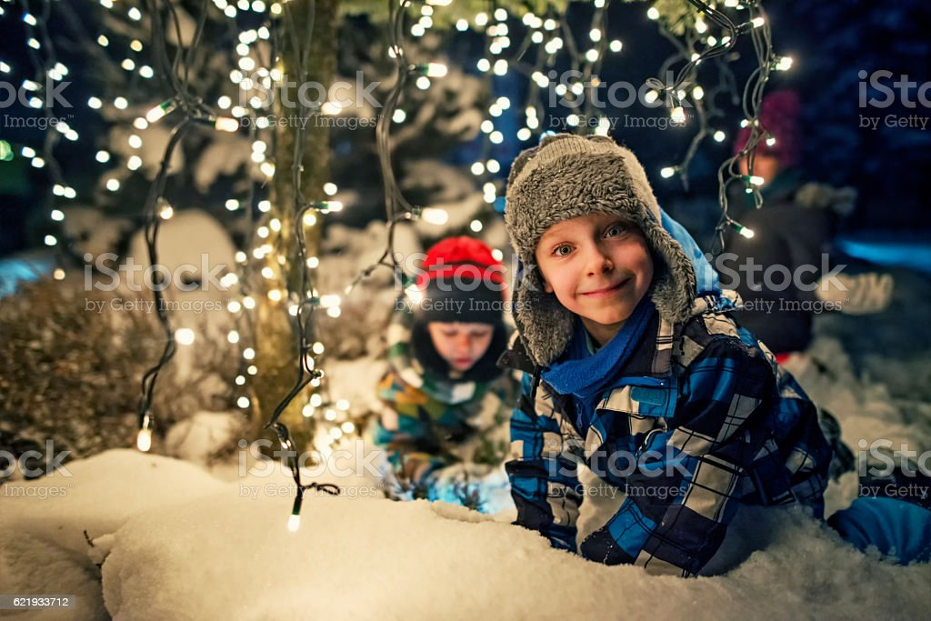 Kids playing in the snowy winter garden under christmas tree stock photo