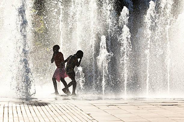Niños jugando en chorros de agua - foto de stock