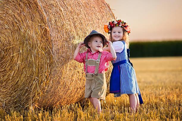 kinder spielen in wheat field in deutschland - bayerische tracht stock-fotos und bilder