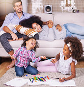 istock Kids playing on floor, parents relaxing on sofa at home 1264117791