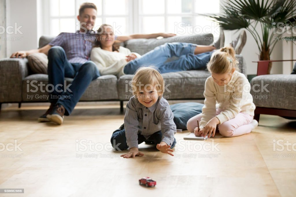 Kids playing on floor, parents relaxing on sofa at home - Zbiór zdjęć royalty-free (Beztroski)