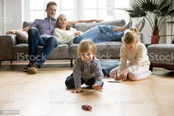 Kids playing on floor parents relaxing on sofa at home picture id938682868?b=1&k=6&m=938682868&s=612x612&h=11ywbw4is s0 dty qossmftwfbridkc8yidsrmwmqg=