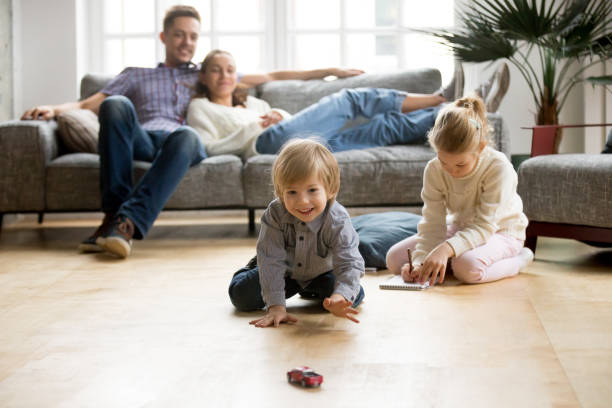 Kids playing on floor, parents relaxing on sofa at home stock photo