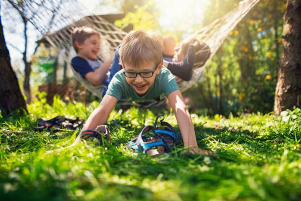 kinder spielen auf der hängematte im garten hinter dem haus - kinder picknick spiele stock-fotos und bilder
