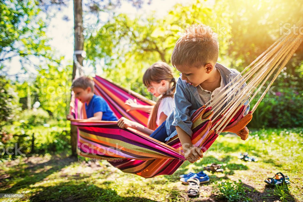 Kids playing on hammock in the garden stock photo