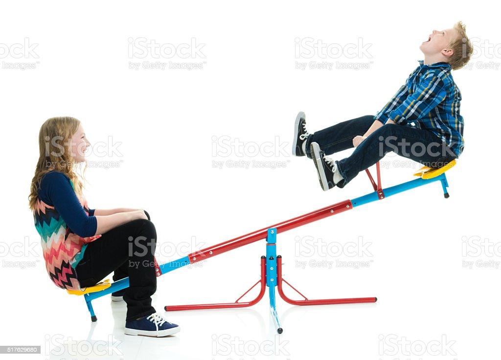 Niños jugando en Teeter totter - foto de stock