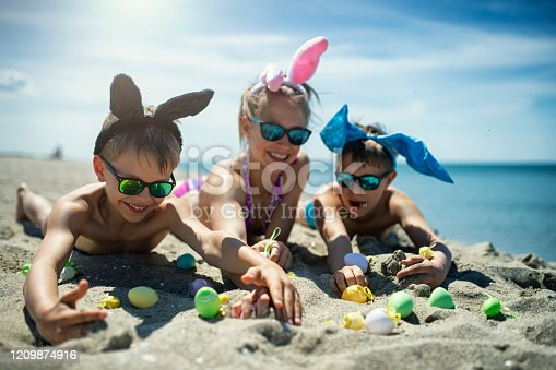 istock Kids playing on the beach with Easter eggs 1209874916