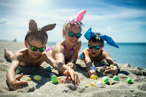 Summer Easter on beach. Kids are lying on hot sand and playing with Easter eggs. Nikon D850