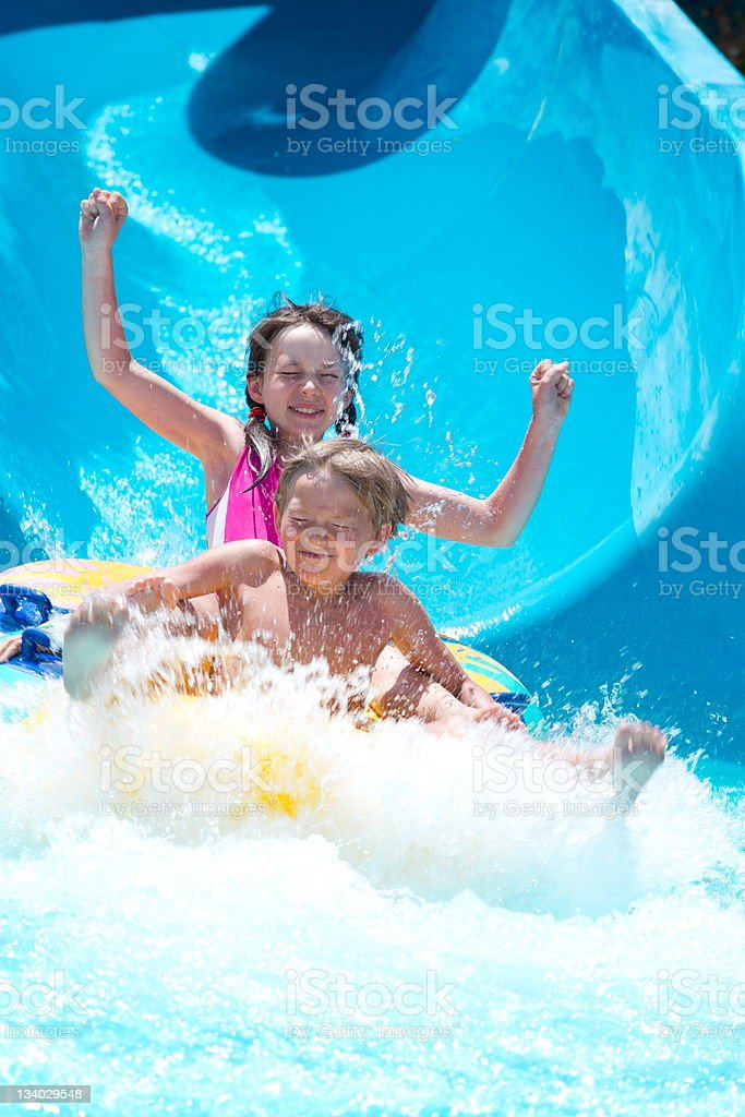 Kids playing on water slide stock photo