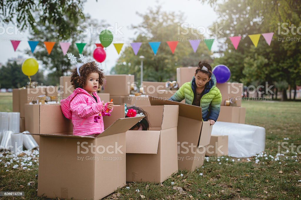 Kids playing outside in the cardboard boxes, stock photo
