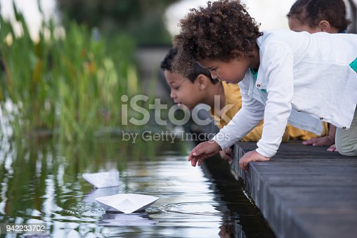 Three kids playing competition with paper boats at a pond.