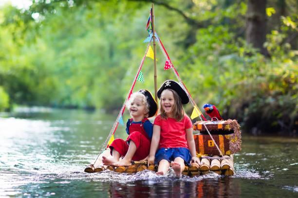 kinder spielen piraten-abenteuer auf floß - matrosin kostüm stock-fotos und bilder