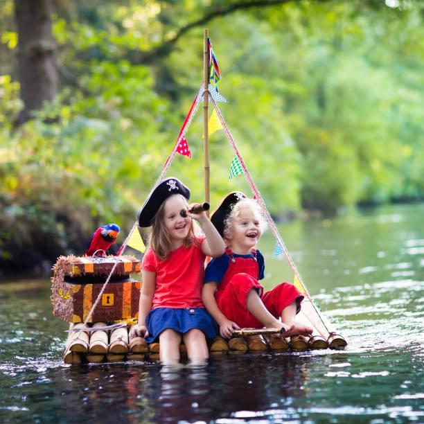 kinder spielen piratenabenteuer auf holzfloß - matrosin kostüm stock-fotos und bilder