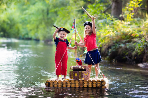 kids playing pirate adventure on wooden raft - pirates stock photos and pictures