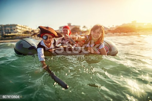 Three little pirates, a girl aged 10 and two boys aged 6 are playing pirates at sea, Father is also dressed up as pirate and is guarding the boat.