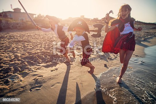 istock Kids playing pirates on a beach 660345282