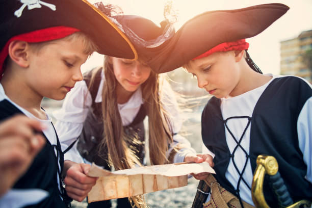 kids playing pirates on a beach - pirates stock photos and pictures