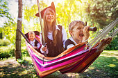 Three little pirates, a girl aged 10 and two boys aged 6 are playing pirates in summer garden, The hammock is their boat. The front boy is looking through a spyglass. The other kids hold their weapons ready. Kids are laughing and having fun.