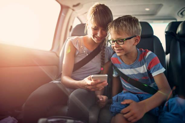 Kinder spielen Smartphone während einer Fahrt – Foto