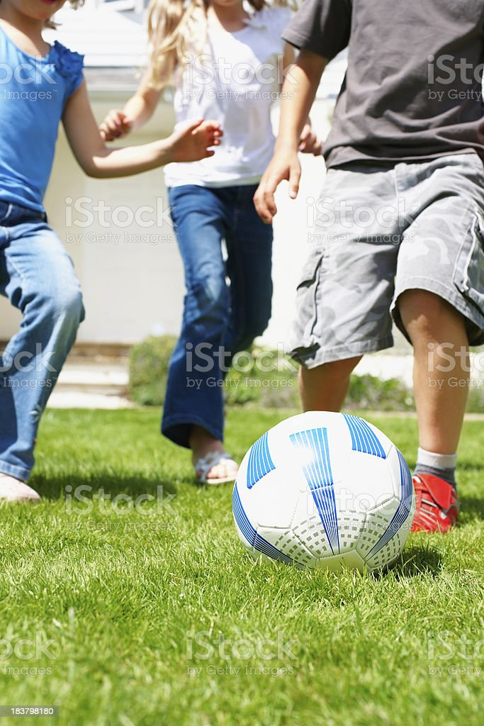 Kids playing soccer on grass royalty-free stock photo