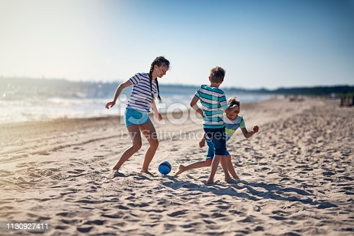 Brothers and sister playing soccer on beach. The boys aged 8 and teenage girl are having fun together on wide beach. Nikon D850