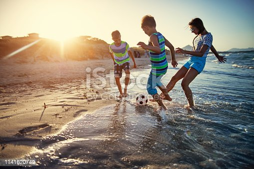 istock Kids playing soccer on on beach 1141620749