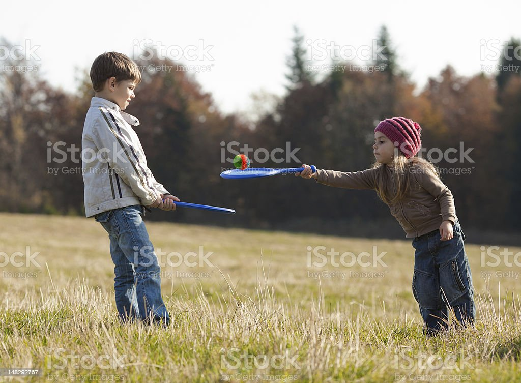 Kids playing tennis outside royalty-free stock photo
