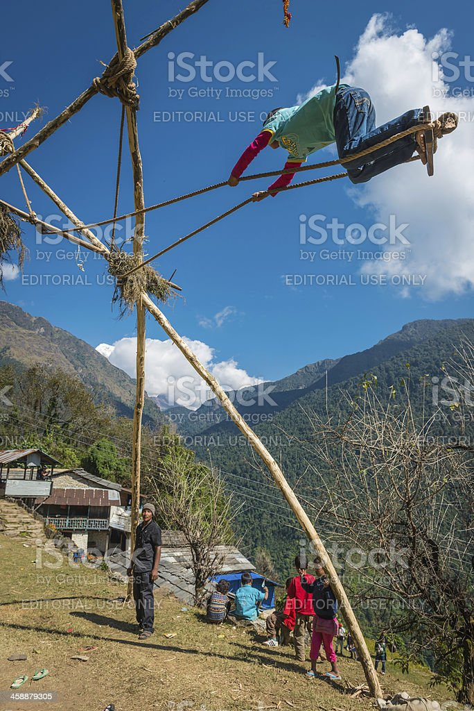 Kids playing traditional swing in mountain village Annapurna Himalayas Nepal royalty-free stock photo