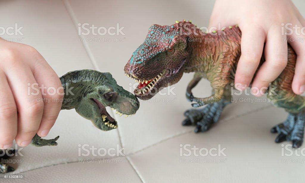 kids playing two tyrannosaurus toys on a sofa at home stock photo