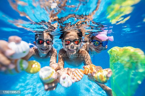 Summer Easter in swimming pool. Kids are playing in water and having fun with Easter eggs. Nikon D850
