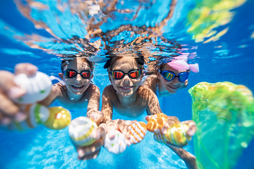 Summer Easter in swimming pool. Kids are playing in water and having fun with Easter eggs.\nNikon D850