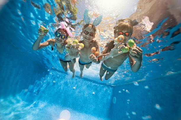 Kids playing underwater during summer Easter stock photo
