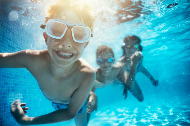 Kids playing underwater in pool Happy kids having underwater party in the swimming pool. The boy is grinning at the camera.  Shot with Nikon D850. swimming pool stock pictures, royalty-free photos & images