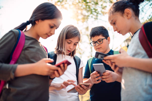 Kids playing video games on smart phone after school Group of kids playing video games on smart phone after school pre adolescent child stock pictures, royalty-free photos & images