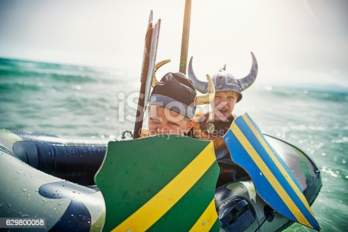 Two fearsome little vikings are attacking enemy, Two boys aged 6 are playing vikings at sea,