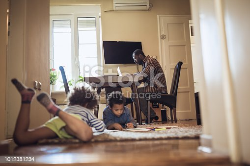 istock Kids playing while their father working at home 1012381234