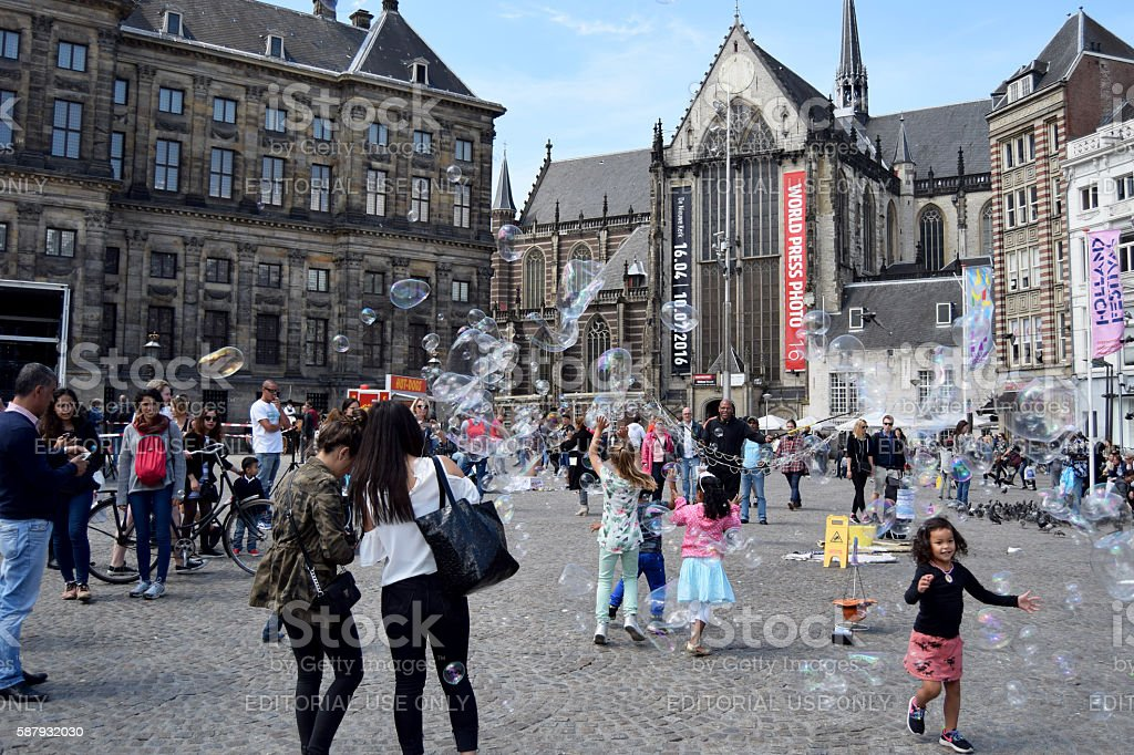 Kids playing with bubbles in the Grand Place of Brussels stock photo