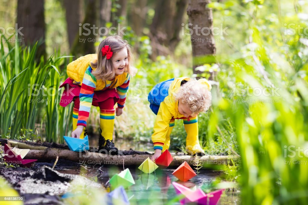 Kids playing with colorful paper boats in a park stock photo