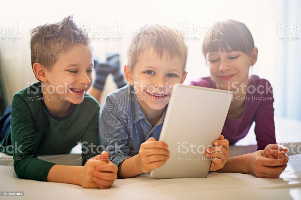Kids playing with digital tablet stock photo