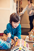 Kids playing with gingerbread house, mother cleaning in background. This is how it is in most family's kitchen. Kids are wearing comfy clothes. Vertical indoors waist up shot with copy space.