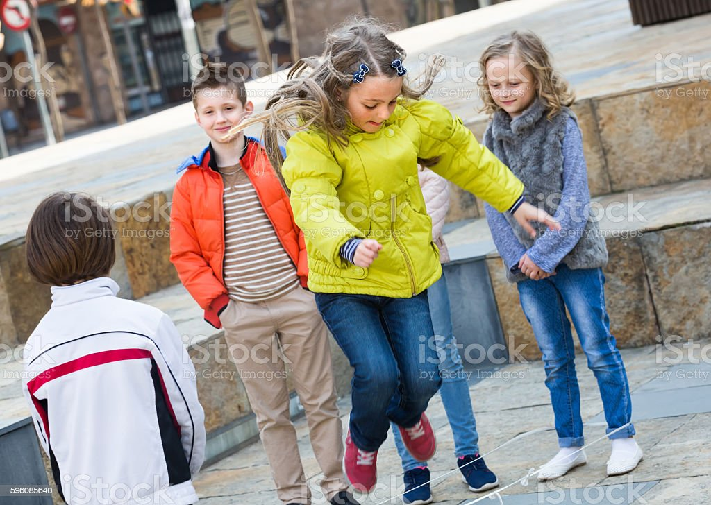 Kids playing with jump rope at street royalty-free stock photo