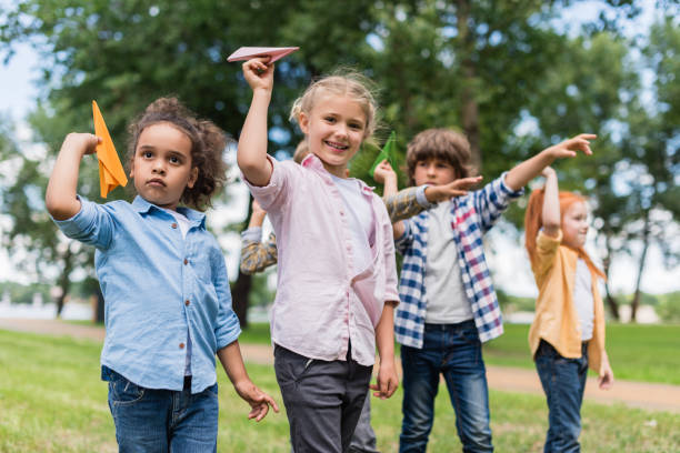 kids playing with paper planes - paper airplane stock photos and pictures