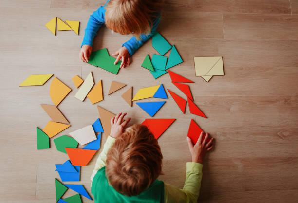 niños jugando con rompecabezas, concepto de educación - foto de stock