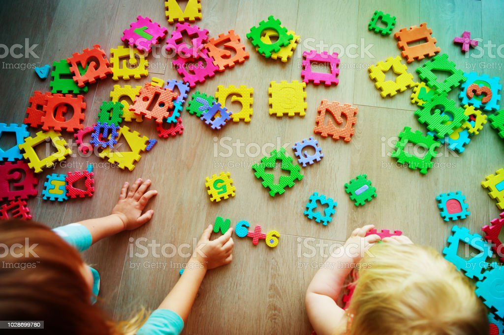 kids playing with puzzle, learning numbers and shapes stock photo