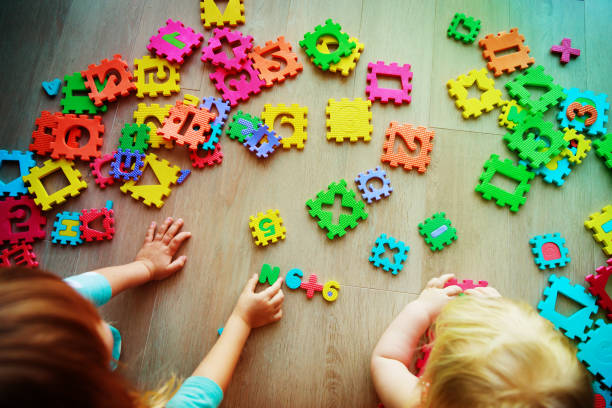 kids playing with puzzle, learning numbers and shapes - infanzia foto e immagini stock