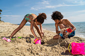 Playful brother and sister are digging a hole in sand on the beach.